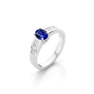 Blauwe saffier 1.15 ct. in 18 karaat witgouden ring met aan beide kanten 3 princess geslepen diamanten.
